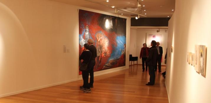 Spettatori interessati osservano la grande tela di Paolo Baratella (sulla sinistra). Sulla destra le piccole opere di Jean Marie Barotte e in fondo i quadri di Verdiana Calia
